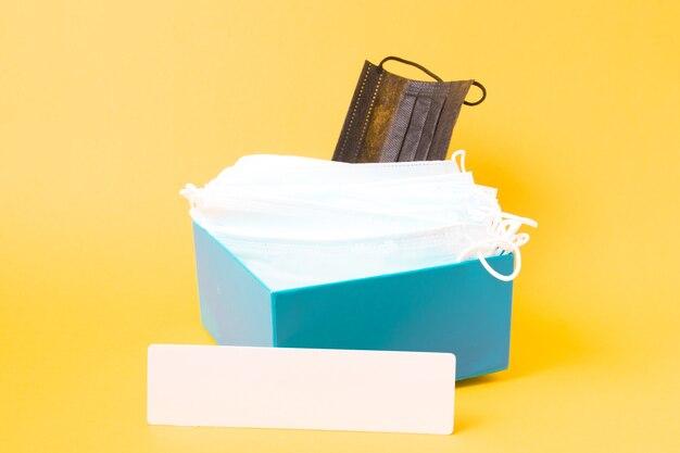 Табличка с надписью и медицинские маски для лица в синей коробке, желтый фон