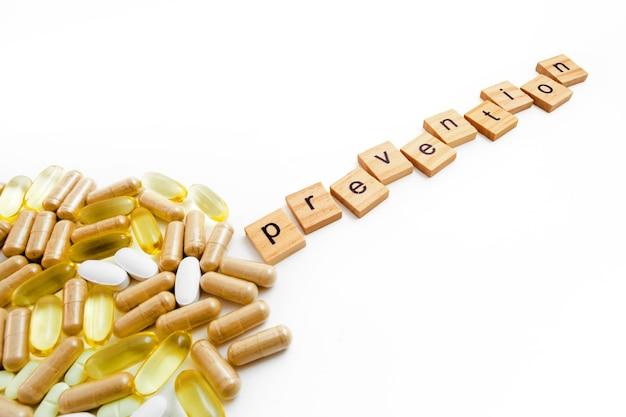 さまざまな錠剤の白い背景の上の木製の立方体の碑文の予防
