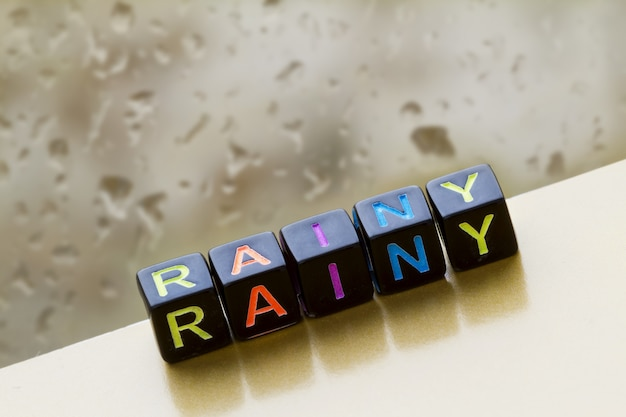 The inscription rainy from toy cubes with colored letters on the background of a window with raindrops.