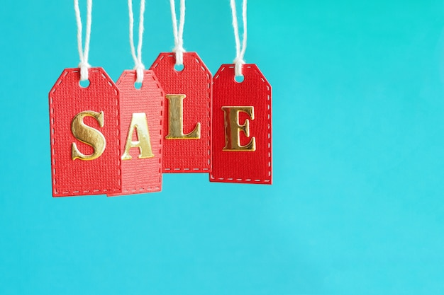 Inscription sale in gold letters on red hanging labels on a blue background