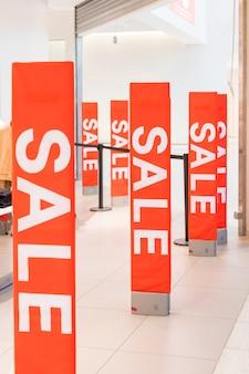 Надпись распродажа на фоне красной стеклянной стены в магазине
