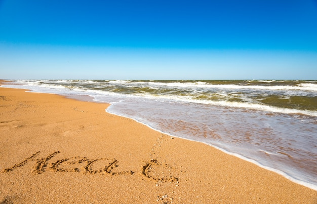 The inscription on the sand summer near the stormy sea wave on a sunny warm summer day. concept of the long-awaited summer holiday and vacation