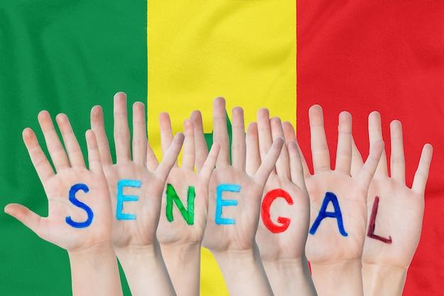 Inscription senegal on the children's hands against a waving flag of the senegal
