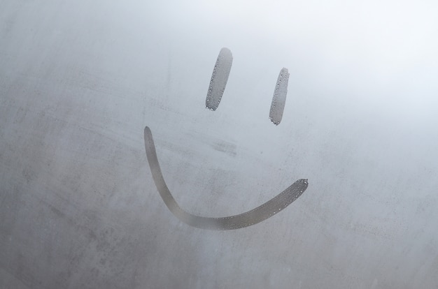 The inscription smile on the misted sweaty glass. abstract background image