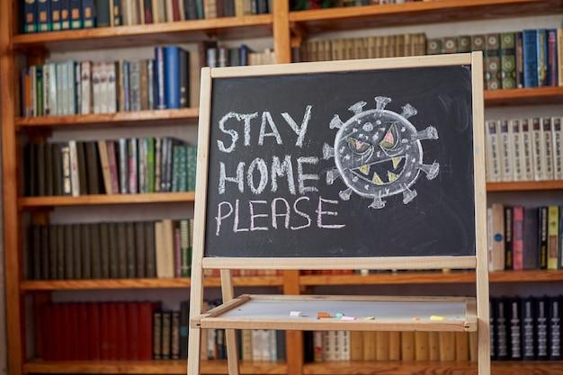 Надпись остаться дома. предупреждение о вспышке. написано белым мелом на доске в связи с эпидемией коронавируса во всем мире. текст пандемии covid 19 на черном фоне с бактериальным рисунком