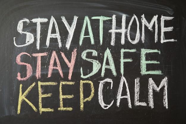 Надпись остаться дома. предупреждение о вспышке. написано белым мелом на доске в связи с эпидемией коронавируса во всем мире.