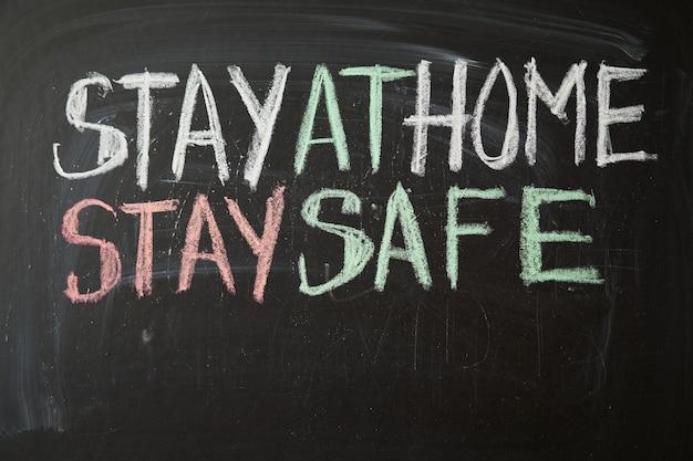 Надпись остаться дома, будь в безопасности. предупреждение о вспышке. написано белым мелом на доске в связи с эпидемией коронавируса во всем мире. covid 19 пандемия текст на черном фоне