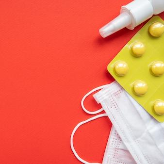 Надпись stop coronavirus. медицинская защитная маска и таблетки на красном фоне. текстовое пространство