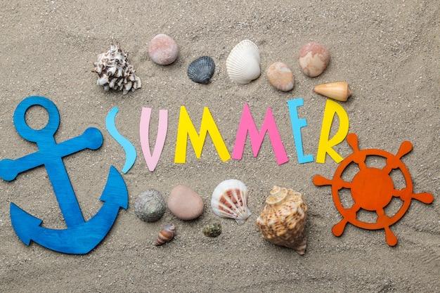 바다 모래에 여러 가지 빛깔의 편지와 조개와 여름 액세서리의 종이에서 비문 여름. 여름. 기분 전환. 휴가. 평면도
