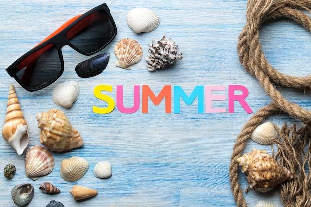 멀티 컬러 문자와 조개와 푸른 나무 테이블에 여름과 바다 액세서리의 종이에서 비문 여름. 여름. 기분 전환. 휴가. 평면도