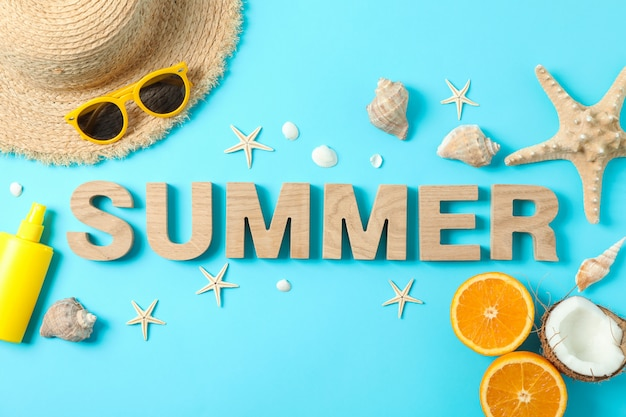 Inscription summer with starfishes, oranges, coconut, straw hat, sunscreen and sunglasses on color background, space for text. happy holidays