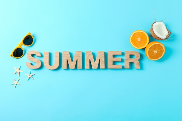 Inscription summer with starfishes, oranges, coconut and sunglasses on color background, space for text. happy holidays