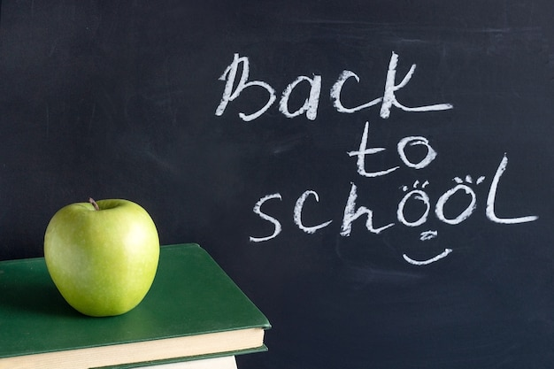 Inscription text back to school on chalkboard and apple on stack books textbooks, concept education