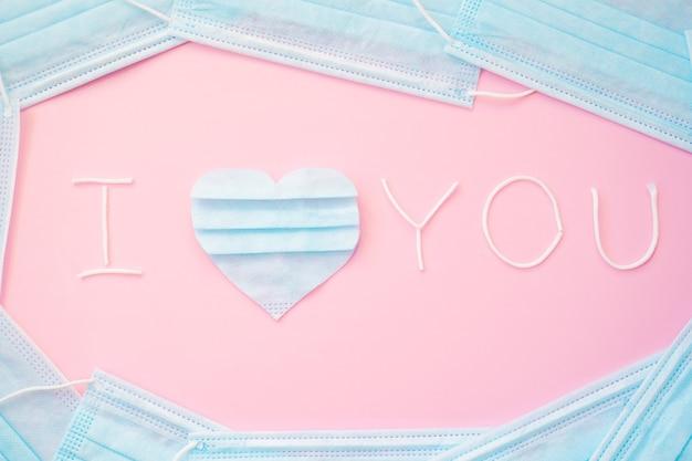 碑文、テキスト使用済みの医療用フェイスマスクの断片から切り取った青いハートであなたを愛しています。