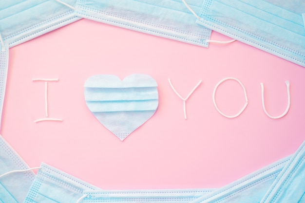 Inscription, text i love you with blue heart made,cut from pieces of used medical face mask.