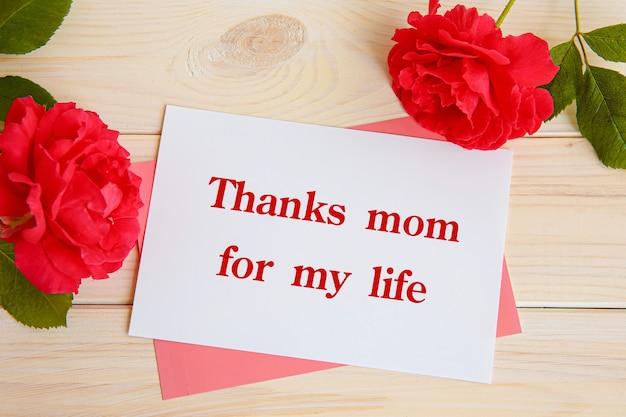 Надпись спасибо маме за жизнь. красные розы и карточка для надписи.