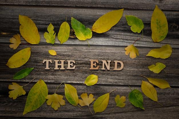 Надпись конец на деревянном фоне, рамка из желтых листьев