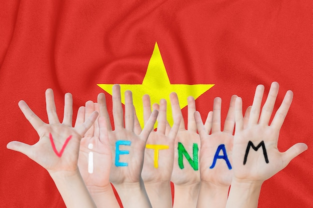 Inscription vietnam on the children's hands against the background of a waving flag of the vietnam