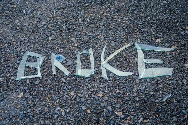 Inscription with broken glass lying on the asphalt.
