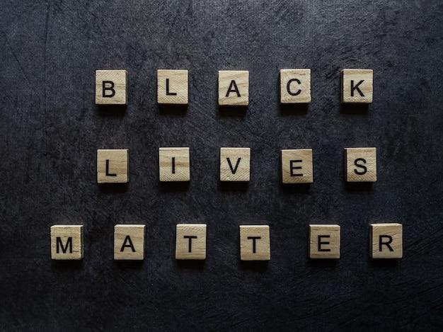 Inscription of wooden letters black lives matter on a dark background.
