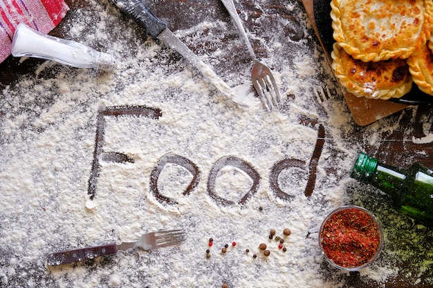 The inscription or word food in english, sprinkled with flour. next fried pies, knife, fork, spices, kitchen utensils. the concept of cooking, baking, home bakery.