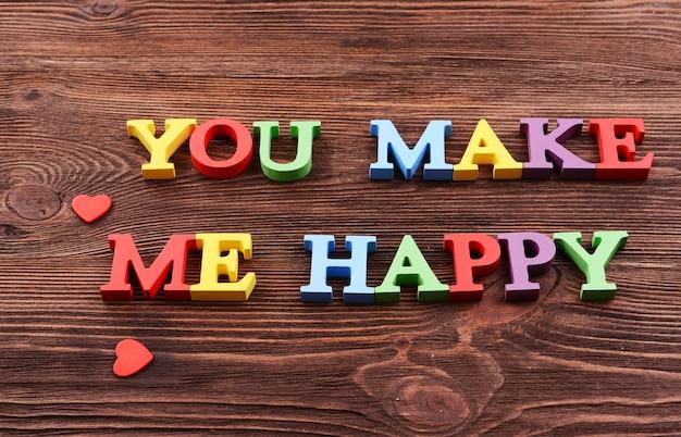 나무 배경에 다채로운 글자로 만든 비문 you make me happy