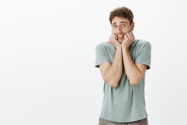Неуверенный и застенчивый забавный парень в повседневной футболке, держится за челюсть и смотрит вытаращенными глазами, имитируя испуг или испуганный страшным фильмом