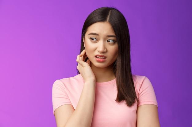 Небезопасная, тревожная молодая застенчивая азиатская девушка нервничает, испугана, царапает шею, встревожена, встревожена сбоку, чувствует опасность, расстроена стоя на фиолетовом фоне страдает дискомфортом.