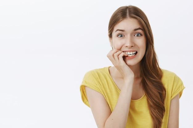 Неуверенная испуганная девушка выглядит нервной и кусает ногти