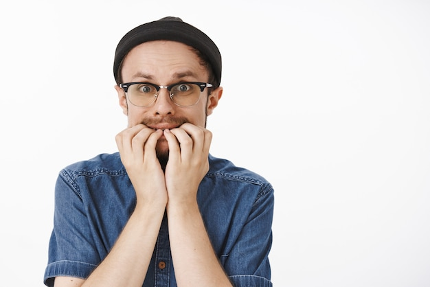 Insecure timid funny man with moustache in black beanie and glasses biting fingernails from fear trembling and panicking being scared