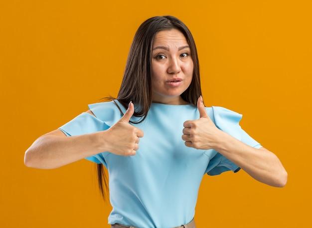 복사 공간이 있는 주황색 벽에 고립되어 있는 카메라를 바라보는 불안한 젊은 아시아 소녀