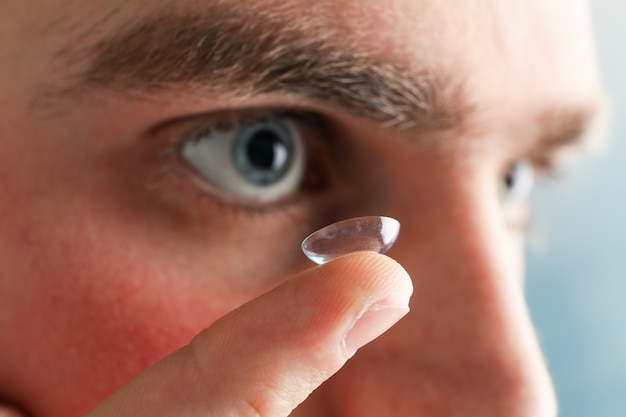 Inserting a corrective contact lens. man with blue eyes