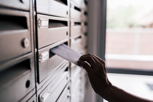 Inserting letter into a building metal mailbox, close-up.