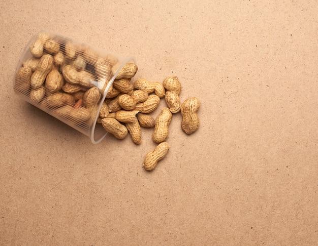 透明なプラスチック製のボウルから飛び散った殻付きピーナッツ