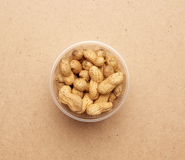 Inshell peanuts in a transparent plastic bowl