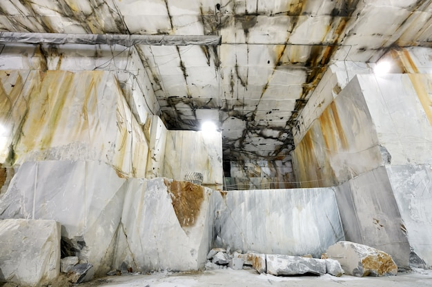 Внутри горной шахты в шахте или карьере каррарского мрамора, демонстрируя ограненные каменные грани скалы в тоскане, италия.