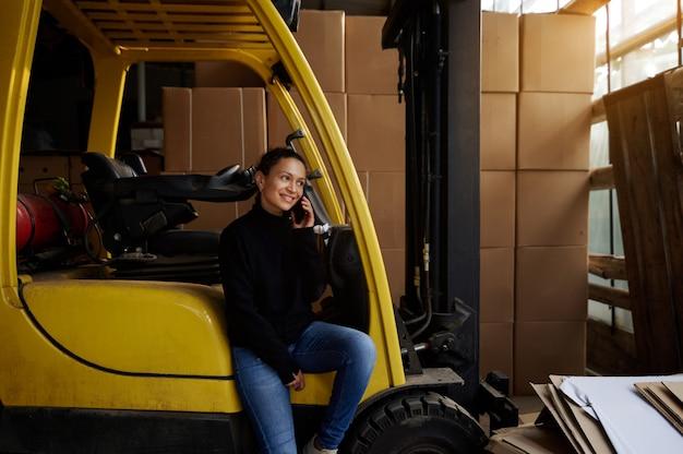 На складе молодая женщина сидит на подножке желтого вилочного погрузчика и разговаривает по телефону.
