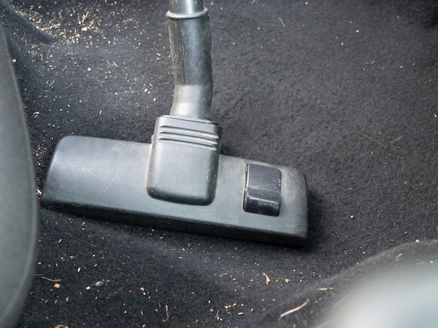 Inside the car cleaning with a vacuum cleaner close-up
