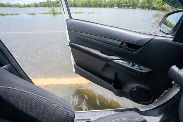 Inside car view, car driving through flooded highway.