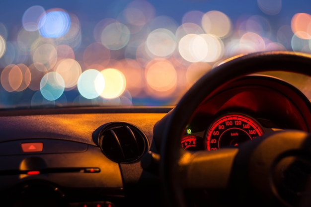 Inside car with bokeh lights from traffic jam on night time for background