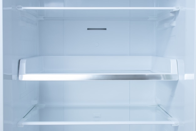Inside of clean and empty refrigerator with shelves.