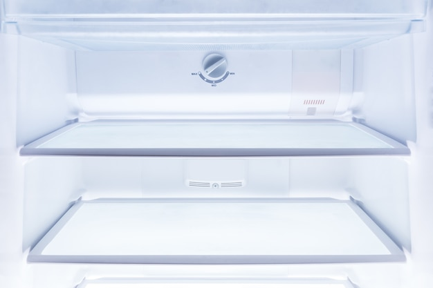 Inside of clean and empty refrigerator with shelves