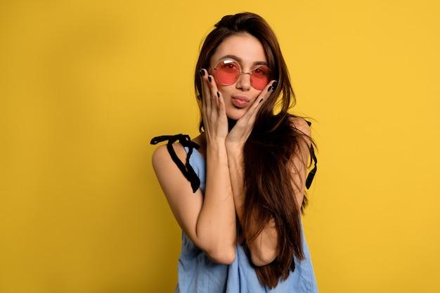 内部の丸いピンクのメガネで魅力的な面白い女の子の肖像画を間近にして顔を作る