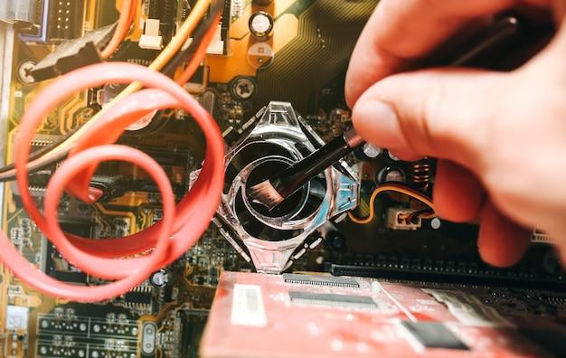 오래된 개인용 컴퓨터의 내부 세부 사항. 먼지에 마더보드와 비디오 카드. 남자가 브러시로 전선을 청소하고 있습니다. 고장난 pc.
