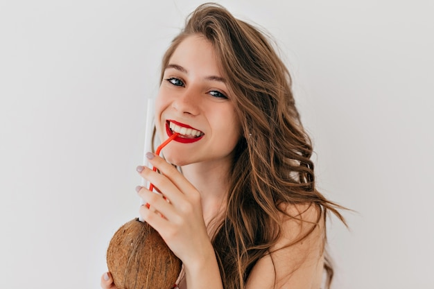 赤い唇と白い歯の幸せなスタイリッシュな女性と巻き毛の健康な肌の中のココナッツを飲むとポーズ