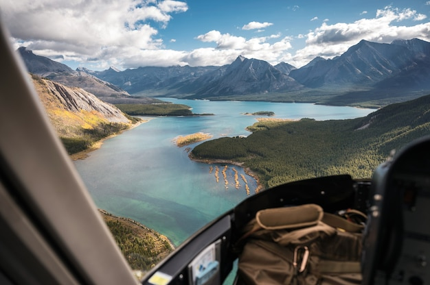 Inside of helicopter flying on rocky mountains with turquoise lake and blue sky in banff national park, canada