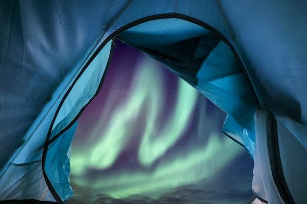 オーロラが夜空を飛んでいる青いテントキャンプの内部