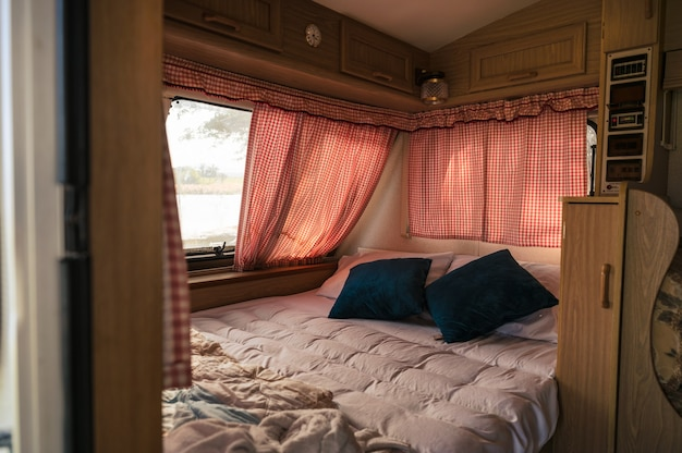 Внутри никого не было автофургона с кроватью, подушкой, занавеской на окне в кемпинге. активный отдых в отпуске