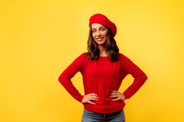 Фотография изнутри молодой европейской очаровательной дамы с короткой прической в красном стильном пуловере и берете, позирующей на желтой стене