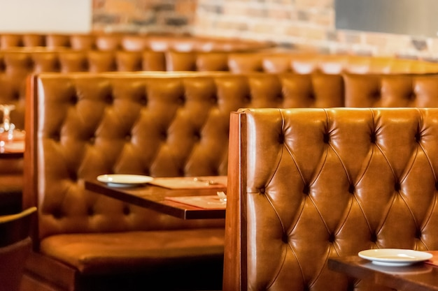 Inside of a restaurant with empty leather chairs and tables